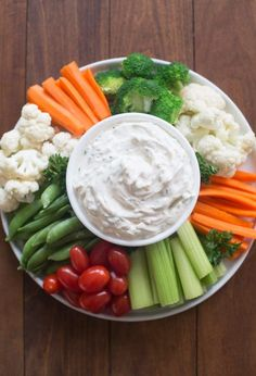 A circular tray filled with vegetables (tomatoes, carrots, broccoli, cauliflower, celery, snap peas) with an easy vegetable dip in the center.