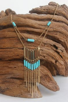 This layered necklace features a gold double chain of turqoise beads, metal bars, and chain fringe. Very unusual and a pretty accent!