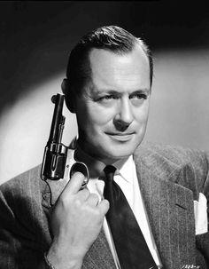 Medium publicity shot of Robert Montgomery as Philip Marlowe holding gun/revolver.