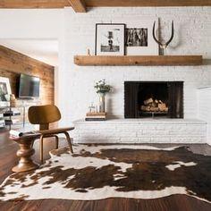 White fireplace + rawhide rug