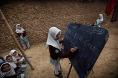 A Pakistani school girl writes on a blackboard during an English class in an outdoor school in a slum near Islamabad. (Muhammed Muheisen/Associated Press) #