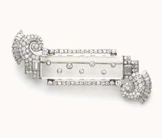 AN ART DECO DIAMOND AND ROCK CRYSTAL BROOCH, BY VAN CLEEF & ARPELS  Set with a rectangular-shaped rock crystal with collet-set diamonds, flanked on either side by a circular-cut diamond bar, to the pavé-set and baguette-cut diamond scrolled terminals, mounted in platinum, circa 1925 Signed by Van Cleef & Arpels, no. 9173