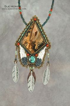 This beautiful cabochon of Sahara picture jasper is accented with a turquoise cabochon, bead embroidered feathers and red jasper beads. The pendant