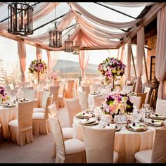 outdoor beach reception with beautiful draping, flowers and hanging lantern chandeliers