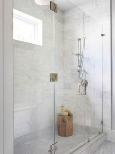 Walk in shower with marble faux tiled wall.