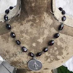 Vintage religious medals and faceted garnets ooak assemblage necklace by Alpha Female Studio.