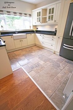 Eastbourne : Cream country shaker kitchen with black granite worktop, grey marble flooring and grey american style fridge freezer