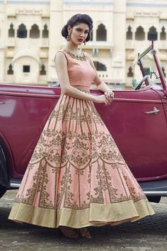 Exude regalia in this appealing peach anarkali suit with a plain torso in art silk bearing gorgeous resham motifs & stone work at the neckline in a graceful design while the waist part is enhanced with a transparent net belt followed by flare in same color featuring brown velvet prints in glorious designs all over the skirt part in a tasteful look, finished by a gold border running all along the flare. This suit is accompanied by matching leggings & dupatta.