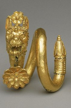 4th Century BC. Greek. Gold and copper alloy spiral earring with lion-griffin head terminal.