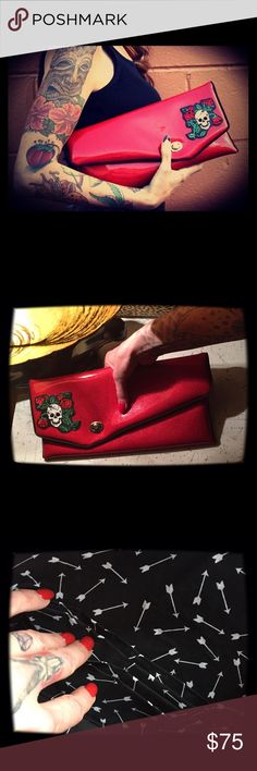 """One of a kind rocking Jess Johnson """"Clutchette"""" New. One of a kind handmade Jess Johnson """"Clutchette"""" . Outside shell is red glitter vinyl with skull & roses trim, black piping, shooting arrows print on the interior. Each clutchette is fully equipped with a built in wallet (six credit card slots-accommodates more than one card per slot, small double pocket perfect for earbuds/coins, and a matching zippered cosmetic pouch to keep all your goodies safe and snug.  💋🤘 Jess Johnson Bags…"""