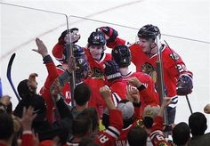 Chicago Blackhawks players including Patrick Kane, Brandon Saad, Duncan Keith and Niklas Hjalmarsson surround Jonathan Toews (lower left) after Toews scored the eventual game winner in the third period as the Hawks beat the Nashville Predators 5-3 in an NHL hockey game in Chicago on Sunday, April 7, 2013.(AP Photo/Charles Cherney)