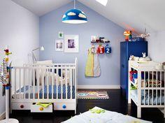 Ein Kinderzimmer mit GONATT Babybett in Weiß mit Schubladen, einem Wickeltisch und einem blauen Kleiderschrank.