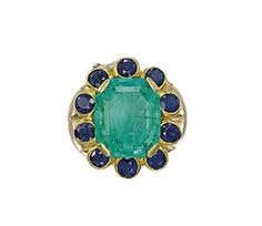 Art Deco AN EMERALD AND SAPPHIRE RING, BY CARTIER  The rectangular-shaped emerald within a scalloped surround of oval-shaped sapphires to the fluted bombé hoop, late 1930s Signed Cartier, Paris