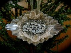 Vintage Tart Tin Ornament with oval rhinestone pin nestled in tea dyed vintage lace and tinsel.  $18.00 https://www.etsy.com/shop/NeedleandThreadLLC