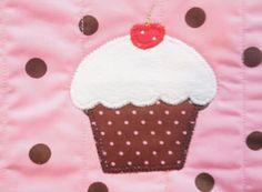 Avental curto em tecido 100% algodão em composê de poá nas cores marrom e rosa, com 02 bolsos lateral. Aplicação de cupcake e detalhe de lacinho.  IMPORTANTE: a imagem é apenas para ilustração de produto, podendo sofrer variações de tonalidade dependendo da configuração do seu monitor e da luz qu...