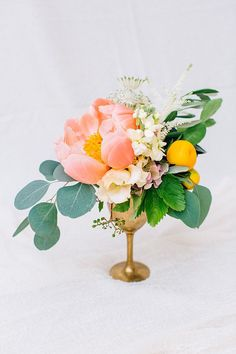 Peonies, lemons, and greenery arranged in a gold goblet | Photo by Tony Gigov