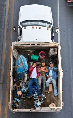 """Men Riding in Trucks"" by Alejandro Cartagena. This is a series of photographs from a Mexican overpass of men riding in the back of trucks."