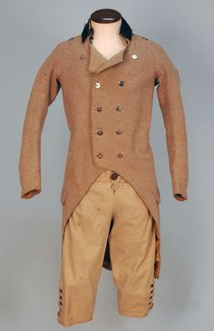 GENT'S EVERYDAY WOOL COAT and BREECHES, 1800-1820. Oatmeal double breasted cutaway style with velvet collar, steel buttons, rear flap pockets, back vent flanked by stitched down pleats having top and bottom button detail, glazed linen lining. Ch-36, W-34, Sh-15, Slv- 24. Fall front tan breeches having three button front, small side buttons, back lacing waistband with pocket, four buttons above buttoned cuff, front lined in green linen. W-26, L-25.