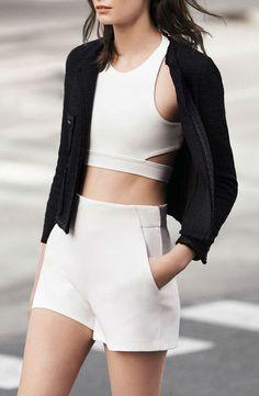 Comprar ropa de este look:  https://lookastic.es/moda-mujer/looks/chaqueta-de-lana-rizada-negra-top-corto-blanco-pantalones-cortos-blancos/2309  — Top Corto Blanco  — Chaqueta de Lana Rizada Negra  — Pantalones Cortos Blancos