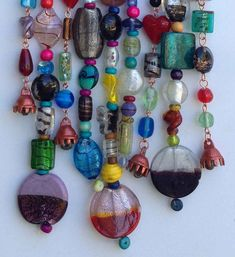 This piece of jewelry for your patio is the perfect way to add colorful shine to your yard. I use mesquite wood and copper wire and 20 lb clear fishing line to string the glass and wood beads. Several of he strands are finished with lovely sounding bells. This piece is very quite so it wont disturb neighbors. This wind chimes can withstand quite a bit of wind but should be cared for during extreme weather. --Measures 5 X 11 --includes a waxed cotton cord for hanging which adds approxima...