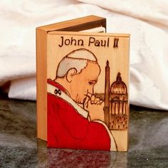 "Wooden Box - Pope John Paul II. Hand-carved rectanular wood box featuring Pope John Paul II on the top of the lid with the Vatican in the background. The box is hand-painted and has various hand-burning techniques used for the outlines of the Pope and the background building. It has a hinged backing for easy opening and closing. The box is ideal for the safekeeping jewelry and precious items. Measures: 5.0"" L x 3.5"" W x 1.5"" H Made in Poland"