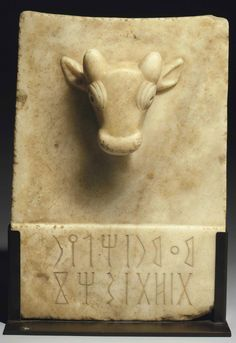 """A SOUTH ARABIAN ALABASTER FUNERARY STELE   CIRCA 1ST CENTURY B.C.-1ST CENTURY A.D.   Rectangular in form, the upper edge concave, a bull head in high relief on the upper end of the obverse, with short protruding horns, prominent ears, large bulging lidded eyes and a rounded muzzle, a two-line inscription in the Qatabanic dialect inscribed on the raised rectangular section at the lower end, reading: """"Memorial of Haliyrit dhat Shahaz"""""""