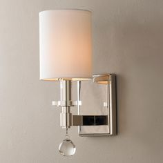 """Modern Crystal Glass Drop Sconce A crystal drop adorns the arm of this classic modern sconce. The squared off corners and straight lines dictate the contemporary style. The polished nickel finish adds to the clean and simple design. 60 watt candle base lamps required. (13.25""""Hx5""""Wx6.75""""D) Shade (6.25""""Hx5""""W) Backplate (5.5""""Hx4""""W)"""
