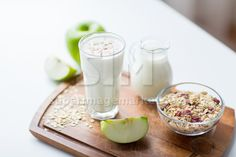 food, healthy eating and diet concept - close up of muesli, milk jug and yogurt in glass on cutting board