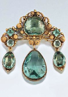 An early 19th century paste brooch Of girandole design set with 'aquamarine' coloured vari-shaped mixed-cut pastes, the shaped surmount with central cushion-cut single stone and square and circular accents within a cannetille surround, suspending triple pear shaped drops, in gilt metal mounts with coloured foil backs, circa 1830, the central drop in open mount: