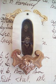 An antique mother of pearl buckle measuring almost 2 1/2 in length serves as a frame for a tintype of a man and woman, a Mr. and Mrs. I named Helen and David. The top of the buckle has a vintage art nouveau style pin attached to the back. The bottom is a very old, antique beautiful possibly rolled gold section of something I believe from the Etruscan period. I have had it for at least 30 years. I shined it up and as you can see it is gorgeous. This is an unusual assortment of different e...