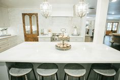 French country kitchen features a pair of white French chandeliers illuminating a gray center island topped with contrasting white quartz lined with rustic backless barstools. Kitchen Images, Magnolia Mom, French Country Kitchens, French Country Kitchen, Home Improvement Projects, New Countertops, Home, Fixer Upper, Asian Home Decor
