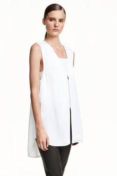 A-lijn bloes: Een mouwloze A-lijn bloes van geweven kwaliteit met een V-hals, een ritssluiting en hoge zijsplitten. De bloes is gevoerd met een korter topje met spaghettibandjes en heeft een overslag op de rug met beklede knoopjes bovenaan.