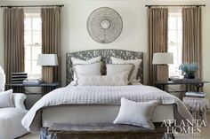 The guest bedroom features an upholstered headboard covered in a cotton fabric by Clay McLaurin and a mounted eel basket, which contributes a rhythmic quality to the room.