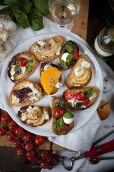 Crostini with gorgonzola & bruschette caprese  Ingredients:  1 bread (ciabatta or baguette)  100g buffalo mozzarella  basil pesto  cherry tomatoes  basil leaves  black olives  100g gorgonzola  1 pear  some dates or figs  1 kaki  some nuts  honey (optional)