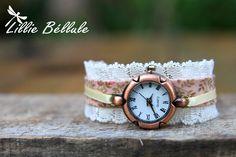 Montre Romance d'antan.  Montre couleur cuivre montée sur un bracelet en tissu liberty vieux rose bordé de dentelle et rehaussé d'un ruban écru. Fermoir boucle et chaînette couleur bronze.