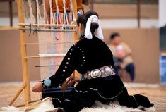 Navajo weaver dressed in traditional womans clothing demonstrates traditional weaving of a Navajo wool rug on a wooden loom in Gallup NM ?