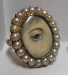 SUPERB GEORGIAN GOLD LOVERS EYE MINIATURE RING WITH HALF PEARLS TO BORDER,  sold for £3.550,00 Ca. EUR 4.479,63