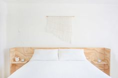 """""""I'd always wanted a (mostly) white bedroom,"""" says Leah. We love the bright, serene effect of the white bedding, floor, macrame (that she made herself!) mixed with the plywood headboard (th Find Furniture, Plywood Furniture, Furniture Design, Plywood Headboard Diy, White Bedding, White Bedroom, Serene Bedroom, Small Space Living, Small Spaces"""