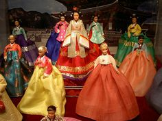 """The much media-spotlighted corner in the Designers Zone is Barbie in Korean traditional dress, or hanbok. The 15 Barbie dolls wearing different styles of Korean court dress stand in a glass-box with the background of the photo of a Korean tile-roofed house. The finely matched pairs of full skirts and jackets are designed by a hanbok designer, Kim Young-seok."""