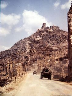 British in Sherman tanks rumble past the ruins of Cassino on the way to the front. Italy