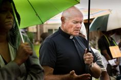 Father Robert Rosebrough, pastor of Blessed Teresa of Calcutta Parish in Ferguson, Mo., prays in the rain during a Aug. 16 service at the site of the death of Michael Brown. The unarmed teen was shot and killed Aug. 9 by a police officer.