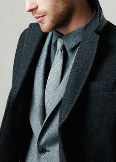 Layer gray on gray for a dapper look this fall and winter. Get the look by pairing a charcoal button down with a light gray plaid wool tie, light gray suit jacket, and fully lined charcoal textured overcoat | Banana Republic