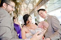"""I let out a chuckle every single time I look at this shot. The combo of the three different kinds of expressions in this shot make it for — adoration from the (presumed) parents, the bride who looks scared she'll break the baby, and the groom making an """"I think he has a dirty diaper,"""" face. Great catch, by Kim Mendoza in the Bay area. http://kmendozaphoto.net/"""