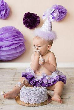 Cake smash photo - pom poms on wall I love the different shades of purple, super cute : )