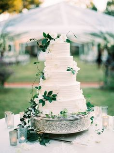 """The bride had always envisioned her wedding in an overgrown garden. """"I was inspired by the home in Great Expectations,"""" says Hillary Hogan. """"Unfussy, natural floral arrangements; antique urns as vases; smilax-adorned French chandeliers; candelabras covered in vines; and outdoor garden furniture."""""""