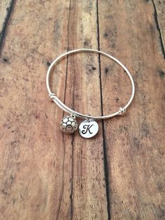 This listing is for a silver plated initial charm bracelet. The soccer ball charm measures 1/2, and the initial charm measures 1/2 in diameter. The