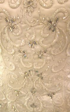 Hand sewn beading and rhinestones on silver embroidery