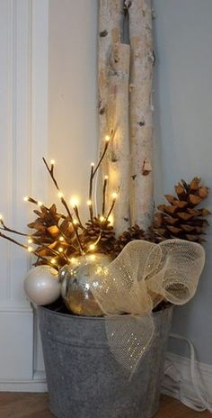 Pinecones, lighted branches, xmas ornament balls and ribbon in a galvanized bucket.