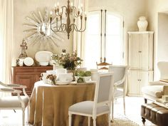 This dining room features serene white and rustic touches, but a sunburst mirror brings a touch of glamour.
