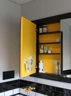 Love the bright color inside the cabinet and what a GREAT way to store tooth brushes and toothpaste!